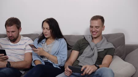 závislost : Diverse young people sitting in row on couch together obsessed with devices online, caucasian addicts using their smartphones, digital life and gadgets overuse concept