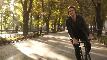 чувствовать : Young caucasian man with headphones riding bicycle in the city park on the trekking black bike. Riding and feeling good while listening to the favourite music. Sun shines on the background