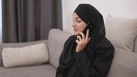 pokrývka hlavy : Attractive muslim woman in black clothes sitting on a grey couch at home and talking on her mobile phone, smiling. Loft interior room