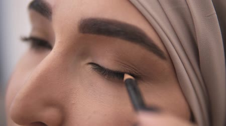 contornos : Extremely close up view of a young muslim woman making an arrow on her eyelid using black eyepencil. Stunning look of muslim woman in beige headscarf