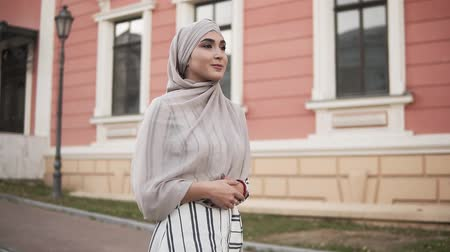 conservative : Confident and attractive woman wearing a hijab. Young woman walking tilt by the city street with beautiful pink and beige building on the background