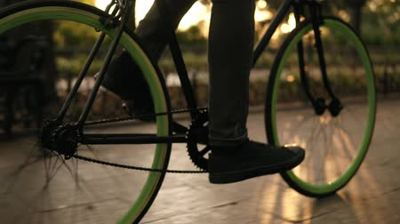 мощеный : Close up footage of male feet cycling a bicycle in the morning park by paved road. Side view of a young man riding a trekking bike with green wheels, wearing black sneakers. Lens flares on the background Стоковые видеозаписи