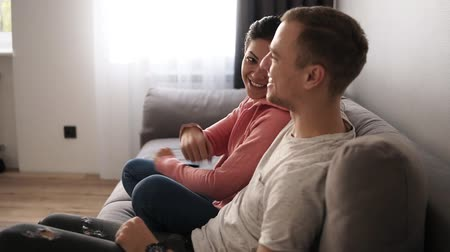 discutir : Young couple watching TV on the grey sofa at home in bright living room. Exciting couple interested on tv show. Side view
