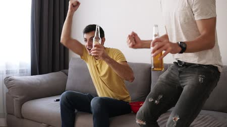 juntar : Two excited adult friends drinking beer and watching football game indoor on tv set with interest. Get up from sofa, emotionally celebrating the win . Close up