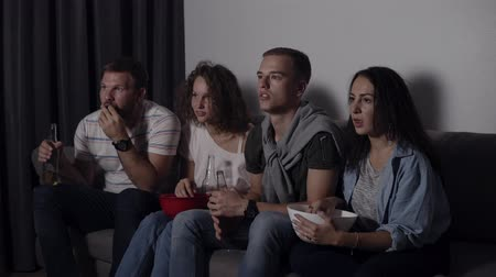 frightful : Best friends eating popcorn, drinking beer watch horror movie together and are very captivated and scared, sit still. Close eyes with hand from scary picture. Movie night Stock Footage