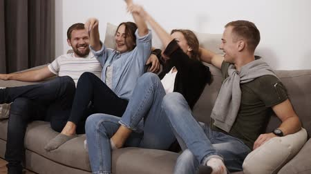 sarılmak : Friendship, communication, party time - cheerful caucasian friends having fun together, embracing while sitting on a grey couch indoors and laughing