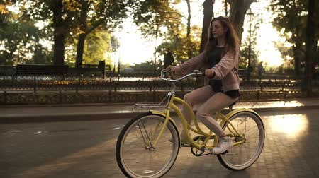 мощеный : Pretty longhaired girl riding a bike on the street or boulevard in summer city park. Wearing pink coloured casual clothes and white sneakers Стоковые видеозаписи