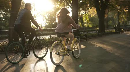 bisiklete binme : Rare view of caucasian young couple or friends riding their bikes in the empty city park or boulevard in summertime. People, leisure and lifestyle concept. Green trees around Stok Video