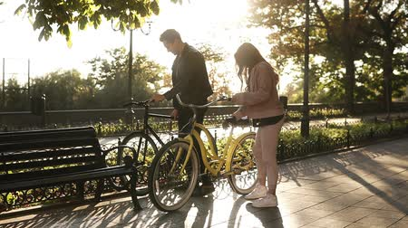 サイクリスト : Beautiful young couple riding their bikes in the empty city park. Stop and sit on the bench and embracing. Loving couple. Sun shines on the background
