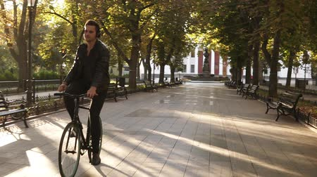 ciclismo : Young man with headphones riding bicycle in the city park on the trekking black bike. Riding and dancing while listening to the favourite music. Trees on the background. Front view Stock Footage
