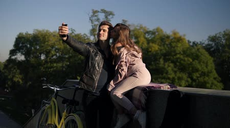 öz : Beautiful young couple taking selfie by mobile phone on street while girl sitting on the parapet. Beautiful couple selfie, love and fun concept. Posing, the girlshowing peace sign. Trees around