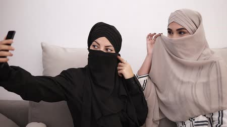 kadınlık : Two arabic women in hijabs - black and beige sitting on the grey sofa while taking selfie picture together at home, closing their faces. White wall on the background