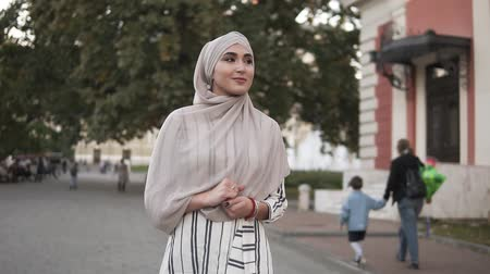 conservative : Confident and attractive woman wearing a hijab. Young woman walking by the city street with beautiful old style buildings and trees on the background. Slow motion