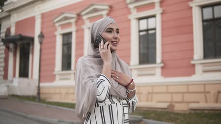conservative : Arab Muslim woman in hijab with makeup walking on the street talking on the phone on a background of beautiful old classic building. The woman is dressed in a stylish clothes