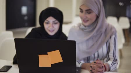parlare : Accelerating footage of happy muslim businesswomen in hijab at office workplace or conference hall. Two smiling arabic woman working on laptop on startup project together, copy space Filmati Stock