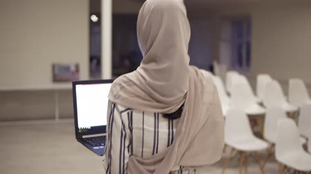 nadir : Young arabic female woman wearing a hijab going by the hall while holding her black laptop in hands. Employee, working place, conference hall, corridor. Backside view