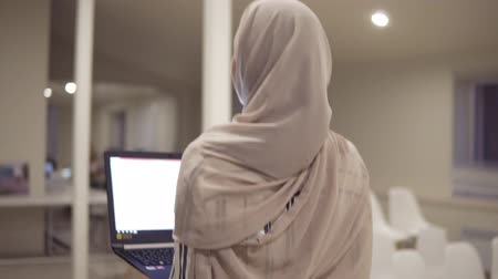 freelance work : Young arabic female wearing a hijab going by the hall while holding her black laptop in hands. Employee, working place, conference hall, corridor. Backside view, unfocused background Stock Footage