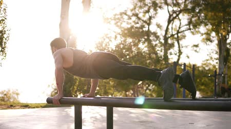 tornász : Athletic young caucasian man doing push ups on parallel bars in local outdoors gym in the park. Man wearing black sports clothes