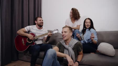 выражающий : Happy friends sit around on sofa and listen to guy playing the acoustic guitar. Get together to have a good time with best friends. Feel the music and rhythm, dancing while sitting, singing