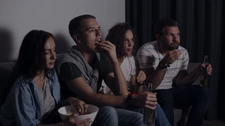 frightful : Four friends eating popcorn, drinking beer watch horror movie together and are very captivated and scared, sit still. Movie night Stock Footage
