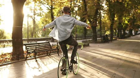 ouvir : Happy young man riding bike in the park and listens to the music in black headphones. Man with outstretched hands. Enjoyment, hanging outdoors in the park. Rare view