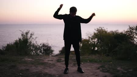 squat : Young brunettte man in black sport suit doing warm up, stretches his arms while standing on the grass. Beautiful scene of morning sunrise under the sea. Front view