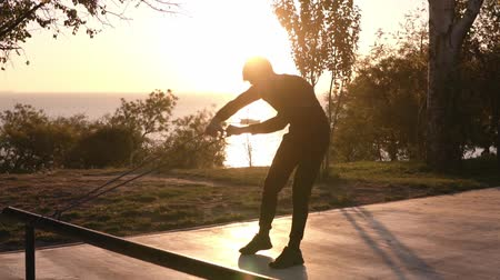 gumka : Silhouette of a man doing arm exercises outdoors using resistance band outdoors in nature. Morning sunrise, outdoors exercises. Slow motion Wideo