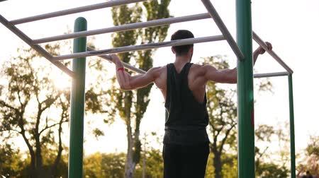 bodyweight : Strong muscular man in black shirt doing difficult pull-ups on horizon bar on sports ground with trees and sun shines on the background. Slow motion Stock Footage