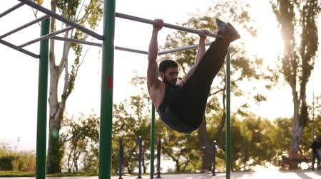 lift ups : Fitness, sport, training and people concept - young bearded man doing legs pull-ups while hanging on the horizontal bar. Abdominal and legs exercise in outdoors gym