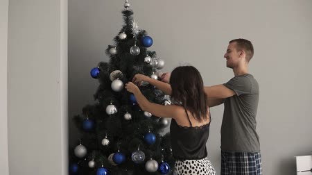 заполнять : Smiling caucasian young couple decorating the fir tree with fancy blue and silver coloured balls. Young family together fill the Christmas tree with toys, preparing for holidays. Loving couple, kissing,happiness. Side view