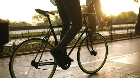 bisikletçi : Close up footage of male legs cycling a bicycle in the morning park or boulevard. Side view of a young man riding a trekking bike, wearing sneakers and jeans. Sun shines, benches on the background Stok Video