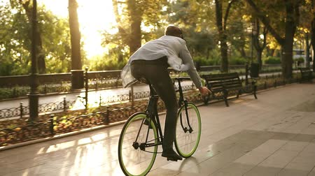 nadir : Rare view of young man riding bike in the park and listens to the music in black headphones. Man riding his bike in the morning. Enjoyment, hanging outdoors in the park Stok Video