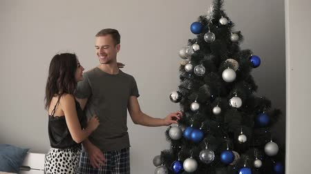 x mas : Smiling caucasian young couple decorating the fir tree with fancy blue and silver coloured balls. Young family together fill the Christmas tree with toys, preparing for holidays. Loving couple, kissing,happiness