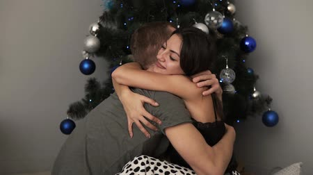 díszített : Young couple staying at home together on holiday evening and sitting on floor near the christmas tree on the floor and hugging. Cute romantic lovers in domestic clothes embracing