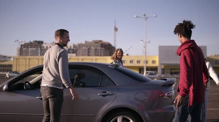 получать : Happy, smiling multiethnic young people get out from the car and walking by parking zone near the malls around. Two couple having time together