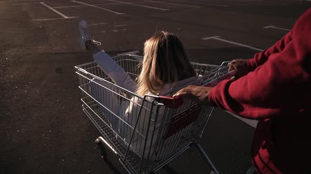 afroamerican : Handhelded footage of a male riding her female friend sitting in the shopping trolley. Close up view of two people having fun outside together on the parking zone