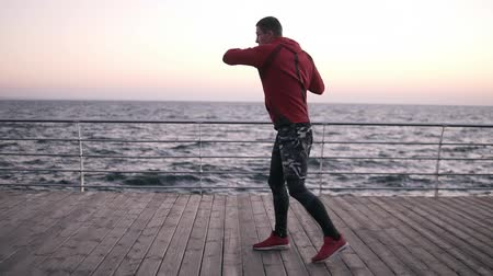 duruş : Professional male boxer outdoor training, standing in fight stance, works hard, making turn torso. Exercising on the open air near the sea