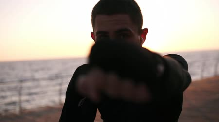 invisible : Front view of a male boxer in black shirt while training process on the promenade in front the sea in the early morning. Portrait of a man boxing with invisible opponent, punching - wearing white earphones. Close up