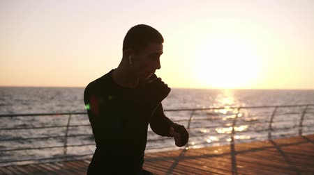 invisible : Gorgeous scene of a male boxer silhouette fighting with invisible opponent in front the sea with morning sun shining behind. Doing punches, exersicing outdoors