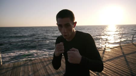 puncs : Front view of a male boxer in black shirt while training process on the promenade in front the sea in the early morning. Portrait of a man boxing with invisible opponent, punching - wearing white earphones. Close up