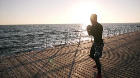 invisible : Young male boxer in black shirt and red sneakers while training process on the promenade in front the sea in the early morning. Man boxing with invisible opponent, punching - wearing white earphones and black bandages on fists. Slow motion Stock Footage