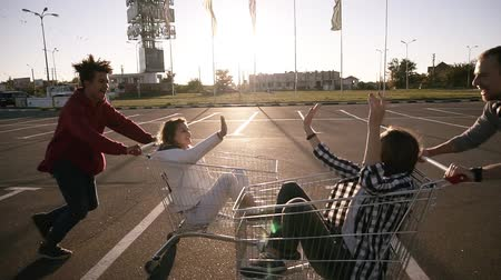 quatro : Young millennials people racing with shopping carts - Happy crazy friends having fun with trolleys in car park. Girls in the corts giving each other high five. Youth lifestyle, friendship and party concept. Sun shines on the background