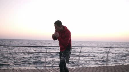 жесткий : Young sportman, male boxer outdoor training, standing in fight stance and making turn torso, lean, stretches his abdomen muscules. Exercising on the open air near the sea