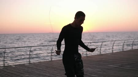 dinleme : Portrait of muscular young man exercising with jumping rope at the seaside. Young man engaged in boxing working out outdoors in white wireless earphones