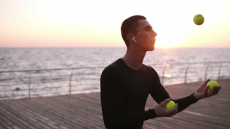 zasnoubený : Sportman improving his reaction - juggling in action, close up. Young man shows performance with yellow tennis balls in front the sea, male performer tossing and catching yellow balls in slow motion, juggling outdoors