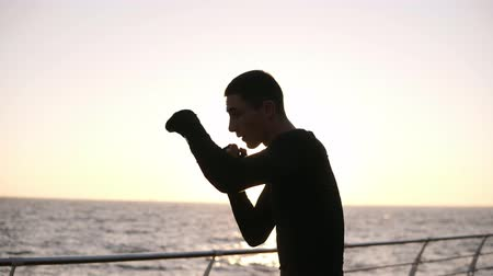 onzichtbaar : Close up view of a caucasian man in boxing bandages on fists traing outdoors. Fighting with shadow, training punches. Endurance, strongness, concentration. Morning sunrise above the sea