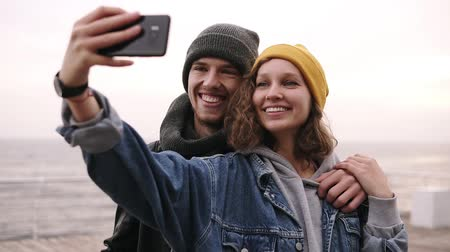 make photo : Happy young couple taking selfie by mobile phone near the seaside in cloudy day. Girl in yellow hat holding the smartphone, making funny faces. Beautiful couple selfie, love and bicycle concept