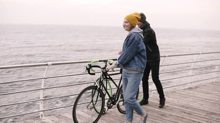 linha de costa : Smiling couple of young hipsters starting walking together with their bikes near the sea at autumn day. Walking by wooden deck in daytime. Sea horizon. Slow motion