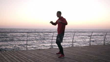 famunka : An athlete warms up during an early morning workout engaged in boxing. Caucasian man exercising, makes torso turns on the wooden promenade near the sea
