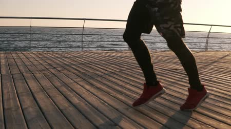 удовлетворенный : Cropped male legs of healthy sportsman wearing sport leggings and sneakers running along pier at seaside during beautiful morning sunrise Стоковые видеозаписи